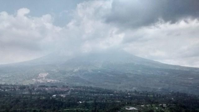 Pemandangan gunung merapi tertutup awan.