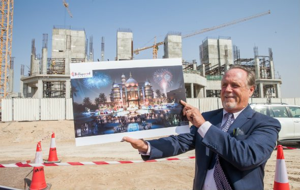 La France holds a picture of Raj Mahal, the structure coming up behind him at the Bollywood theme park. Raj Mahal, an 800-seat theatre, will host live shows every evening with a 150-member cast.