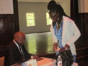Congressman James E. Clyburn signs a book for Queen Quet