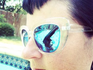 Reflection of a revolver in the sunglasses of a woman standing by the pool