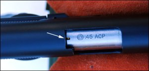 The Expert's loaded chamber indicator shows a cartridge rim in the slot at the rear of the barrel.