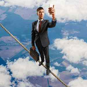 A accountant is standing on a tight rope while holding up his phone