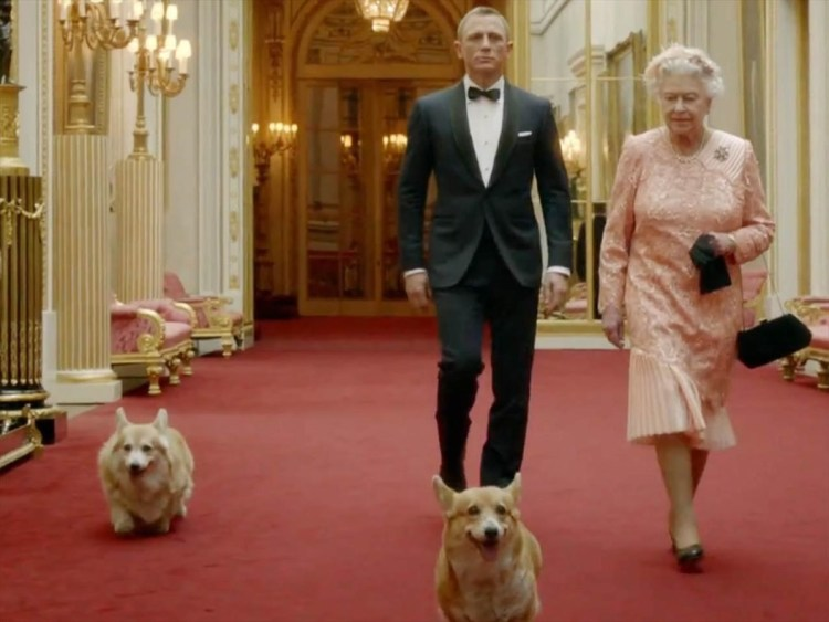 Queen Elizabeth II with two of her dogs next to James Bond