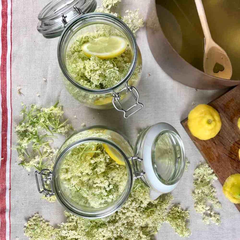 Blüten und Zitronen in den verschließbaren Gläsern aufteilen.