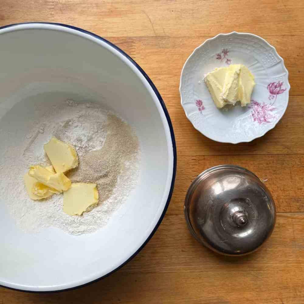 Schneide Stückchen von der kalten Butter in die Mehlmischung.