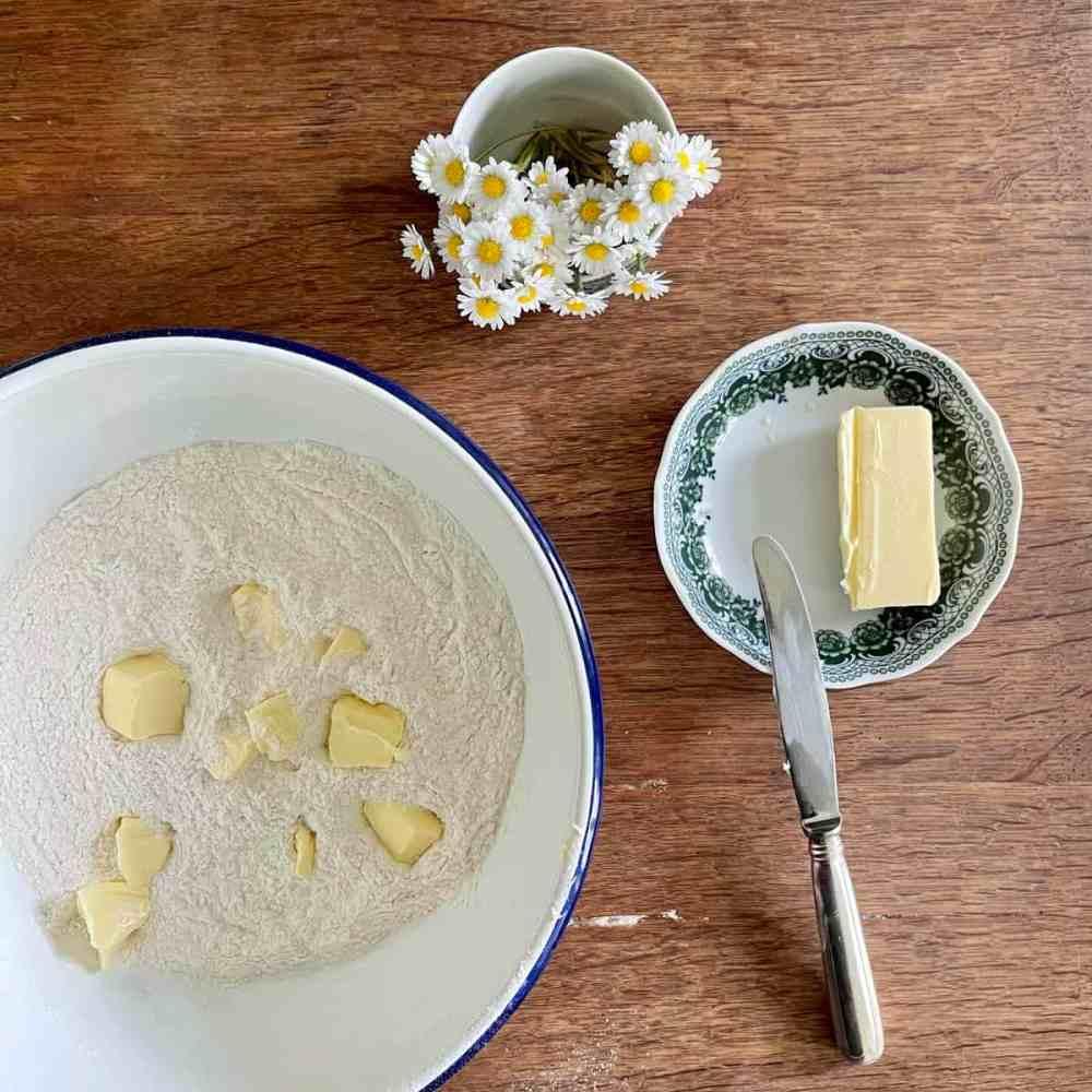Butter in Stücke schneiden und in einen Teig vermengen