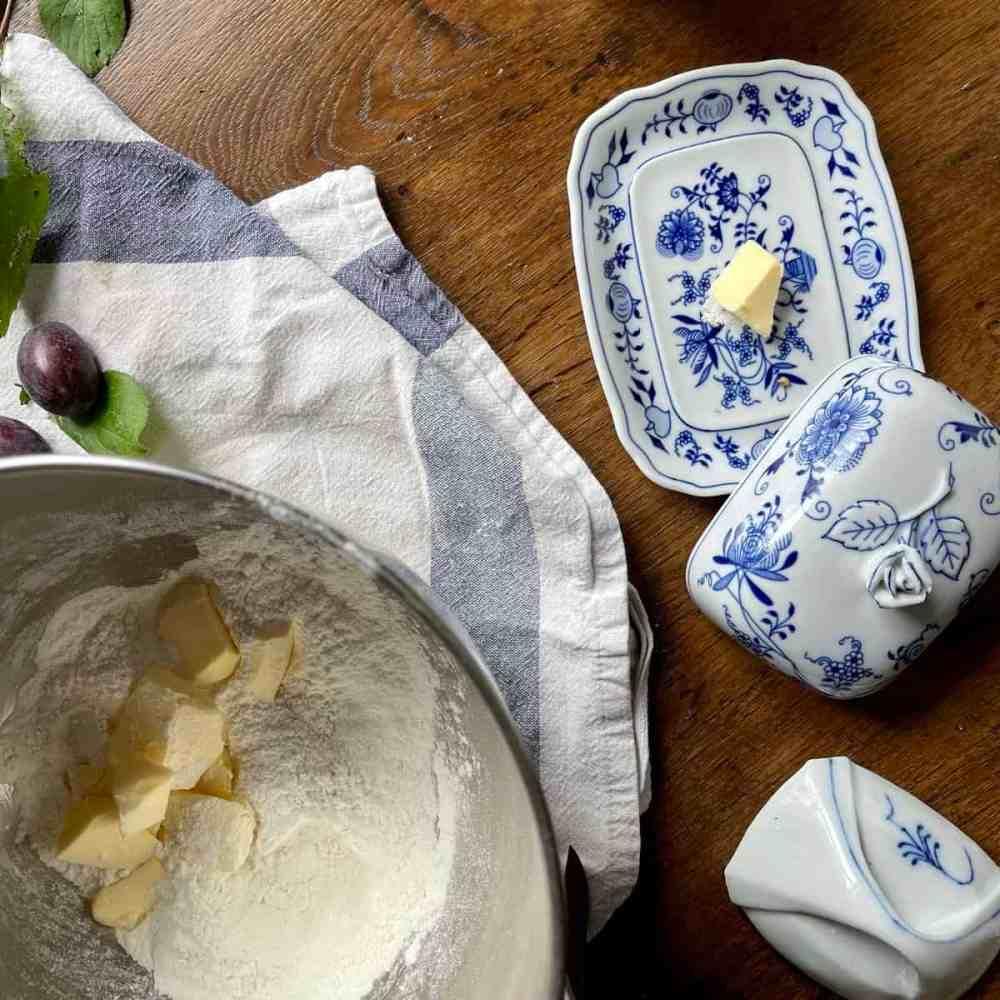 Schneide kleine Stückchen von der kalten Butter in die Mehlmischung.