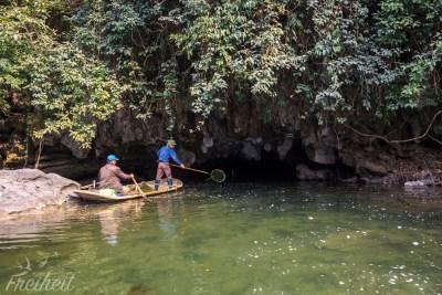 Zwei Männer beim Saubermachen vorm Höhleneingang