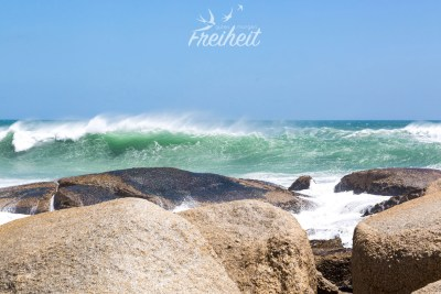 Noch während die Welle bricht, trägt der Wind schon wieder die Gischt weg