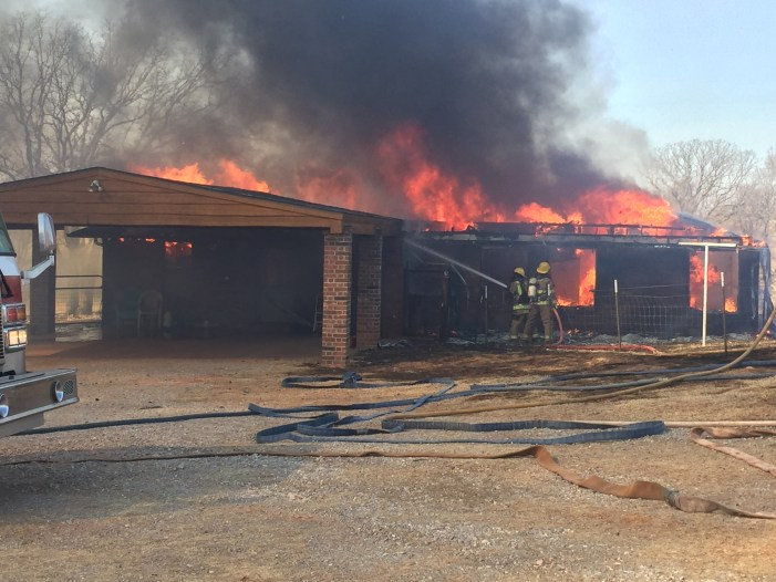 House fire turns into large grass fire in southern Logan County