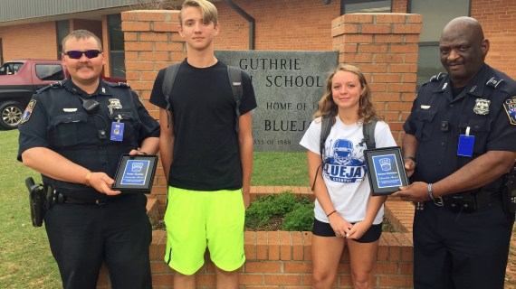 Police officers deliver Citizenship Award to teens for integrity