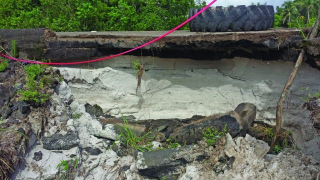 The damage to the curb wall along the highway