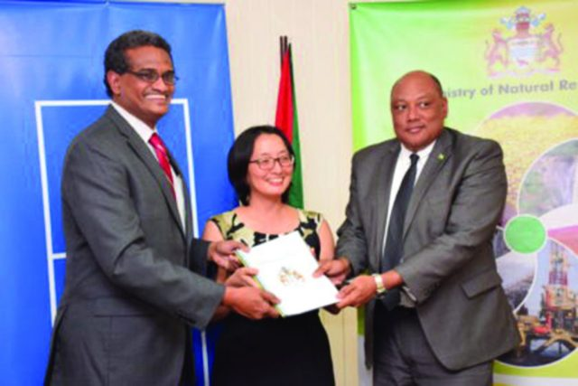Natural Resources Minister Raphael Trotman receives the readiness assessment report from Principal Consultant of the Association of Caribbean Energy Specialists, Anthony Paul and UNDP Resident Representative, Mikiko Tanaka