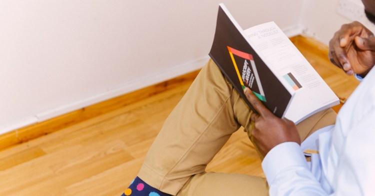 homme assis lit un livre