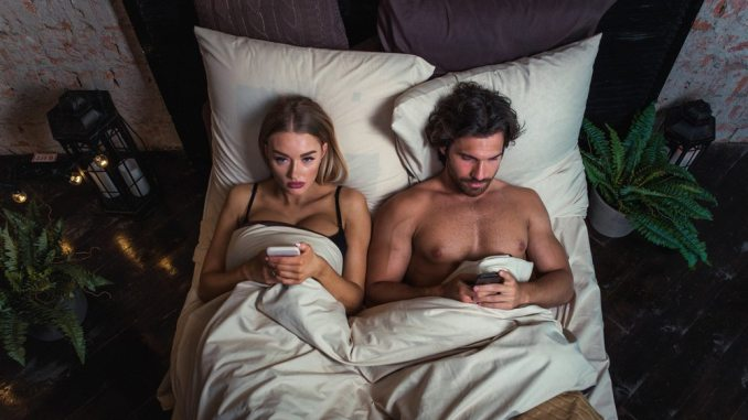 couple in bed on cellphones looking unhappy