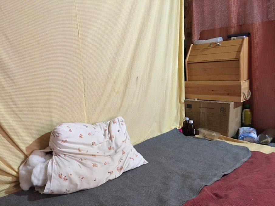 C'est dans cet assemblage de planches de bois, de tissus et de couvertures que vit Hussain. Crédit : DR