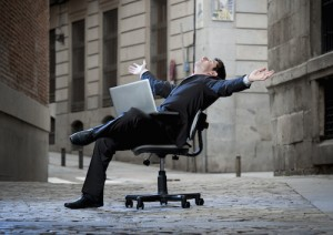 Happy relaxed Business Man sitting on Office Chair on Street with Computer