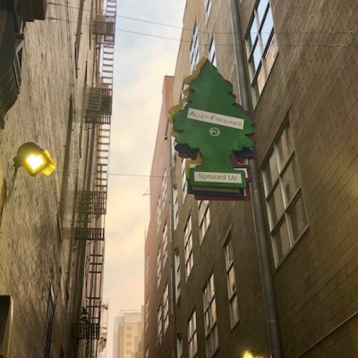 Art installation that looks like giant air fresheners hanging over an alleyway