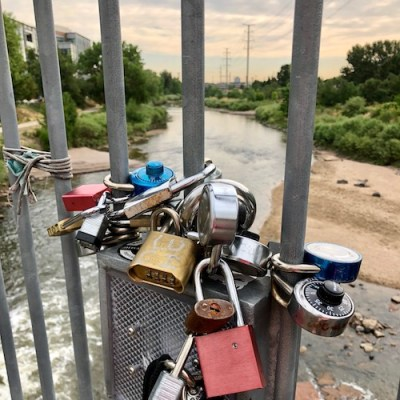 Locks attached to a bridge railing overlooking the South Platte River