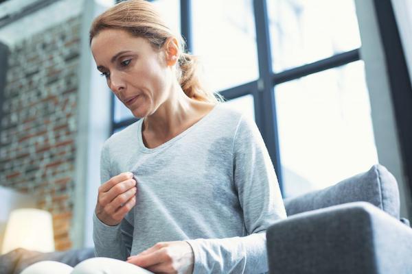 Menopauza tüneteivel (izzadás, hőhullám) küzd egy hölgy kanapéján ülve.