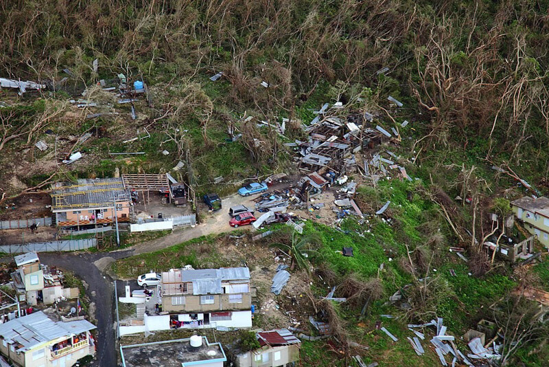 Destroyed homes in Puerto Rico in the aftermath of Hurricane Maria, prompt questions about the appropriateness of travel amidst tragedy.