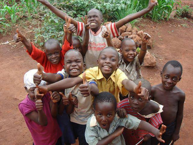 Group of children in Africa reaching out with smiles