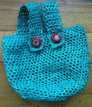 Green plarn bag with red bottle top buttons