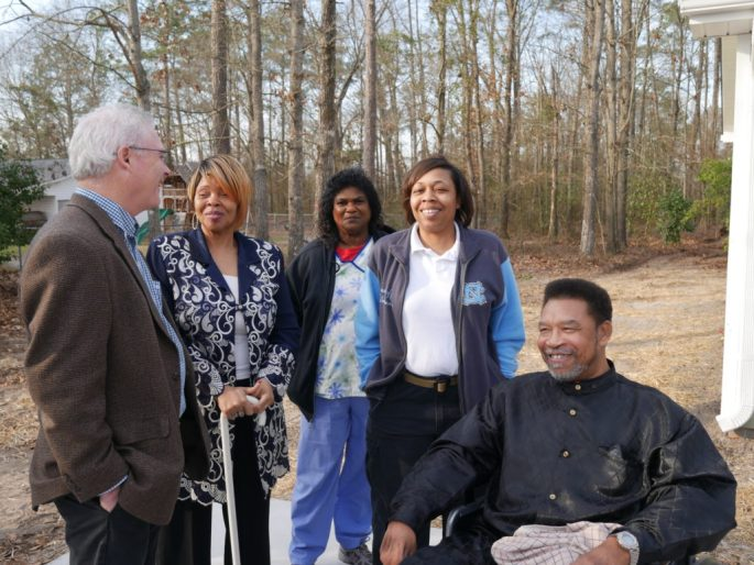 Greg Kirkpatrick, executive director of Habitat North Carolina, speaks with Regina and Bobby McDonald before the dedication.