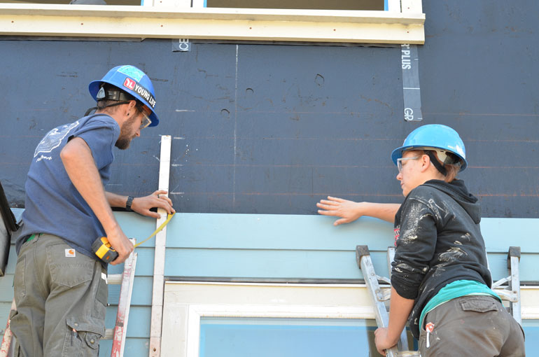 Americorps members work on a siding project.