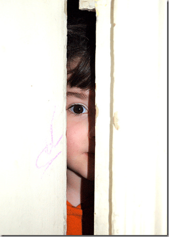 Enfant qui regarde par une porte