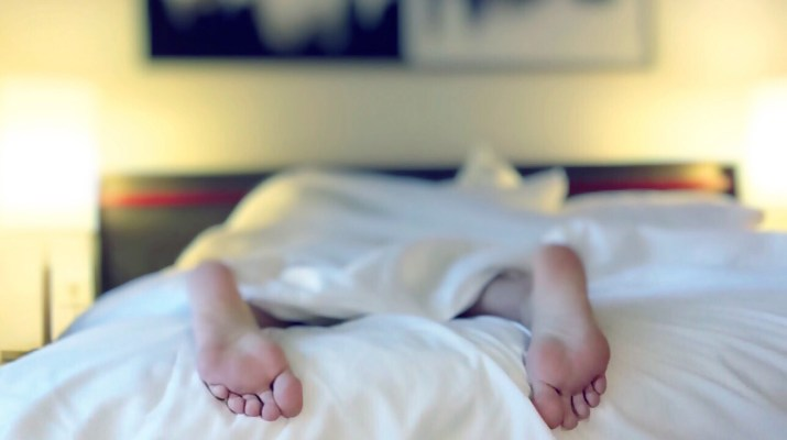 Person's feet sticking out from sheets on bed