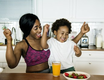 Mother and son eating strawberries and orange juice