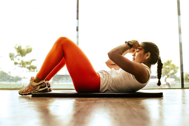 Photo of woman in white and orange workout clothes performing sit-ups