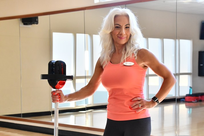 Judy posing with a Les Mills barbell