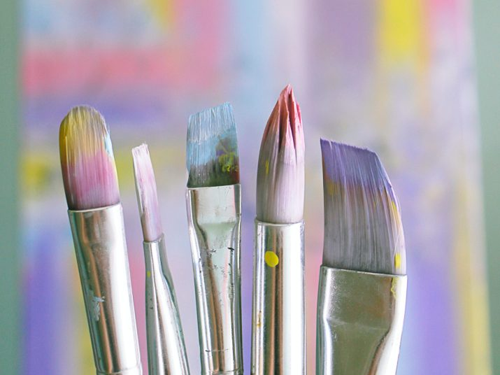 Close-up photo of five colorful paintbrushes of various sizes