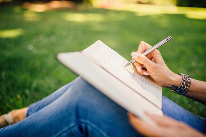 Close-up photo of woman sitting in the grass and writing in a journal