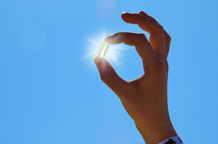 Photo of a hand holding up a translucent yellow pill in front of the sun.