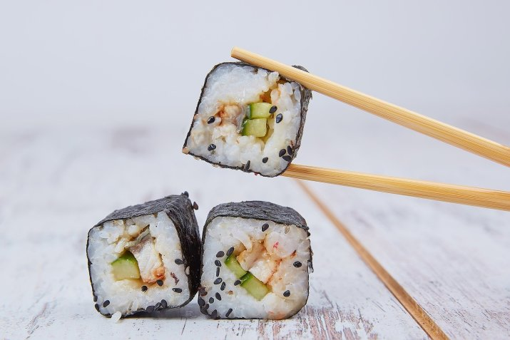 Close up photo of three pieces of sushi, one of which is being picked up with chopsticks.