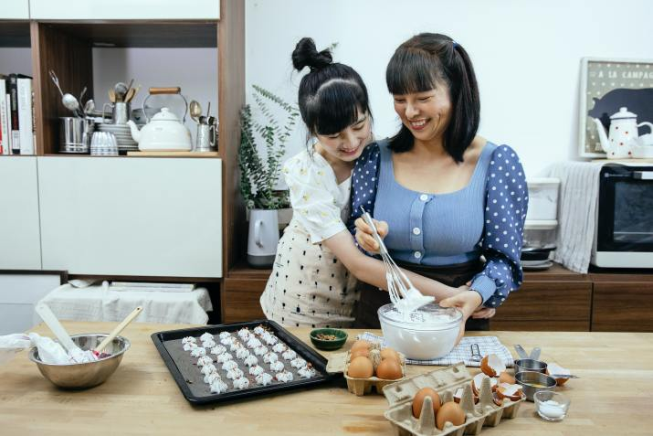 Woman whisking eggs and other ingredients in the kitchen with her daughter