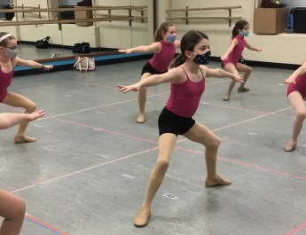 Young girls in red leotards and black shorts participating in a dance class