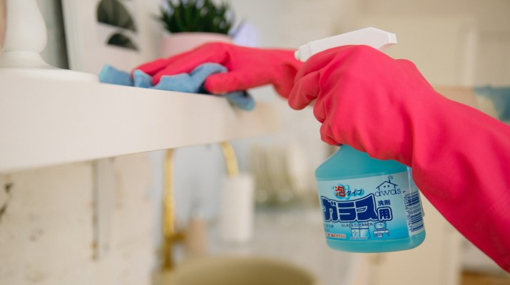 Person wearing pink gloves cleaning kitchen shelves with spray cleaner