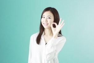 指で輪を作る女性