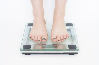 正月太りが気になって体重計にのるイメージ