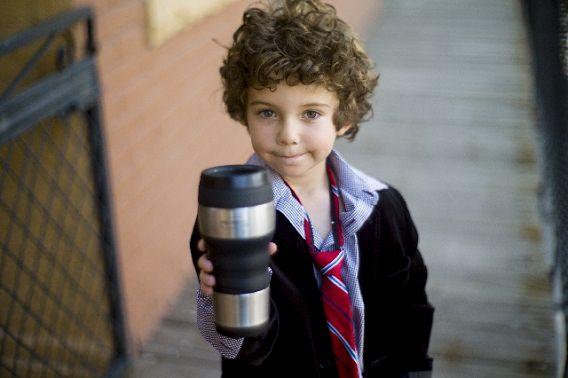 タンブラーでジュースを飲む子供