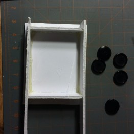 Build a box using hot glue and foam core to fit your mold.