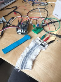 Playing music with a knitted stretch sensor made by Becky Stewart in her Sound Processing with Bela workshop.