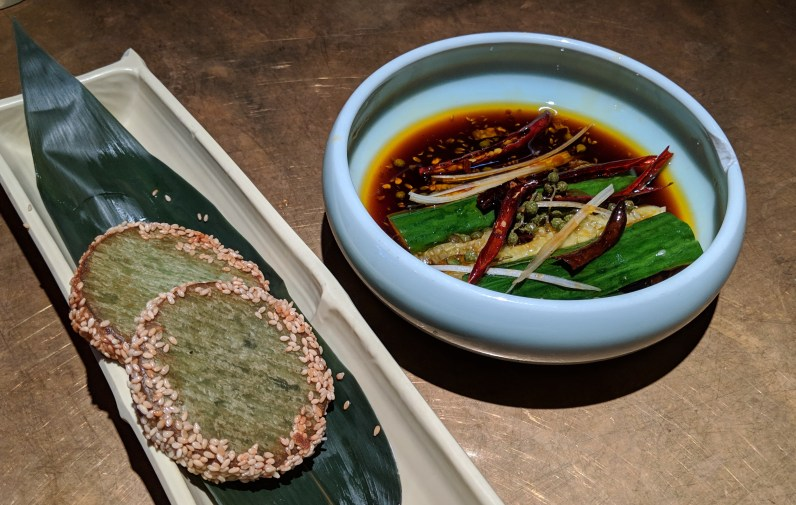 Delicious rice paste patties with seasame seeds, and cucumber in soy and spicy pepper