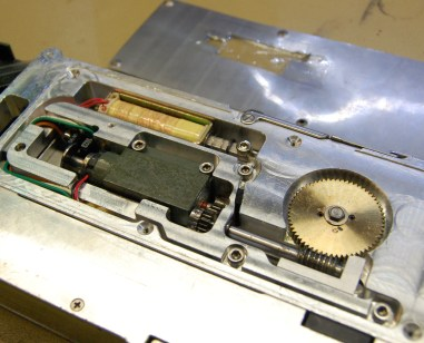The feed mechanism, with sprocket gear on the left, motor bottom right, and solenoid top right.
