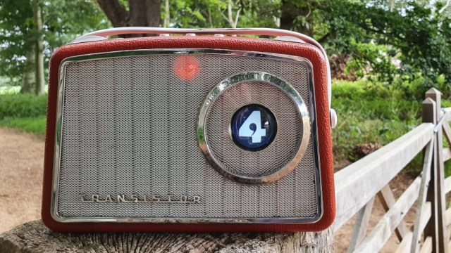 Front view of vintage radio, with small screen inset into tuner.