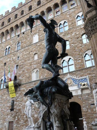 Perseus mit dem Haupt der Gorgo Medusa von Cellini in der Loggia dei Lanzi, im Hintergrund Michelangelos David (in Kopie) vor dem Palazzo Vecchio